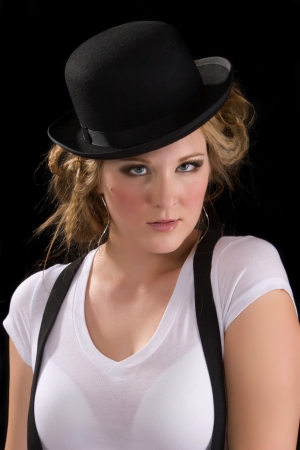 woman wearing a white tee shirt, suspenders and black bowler hat