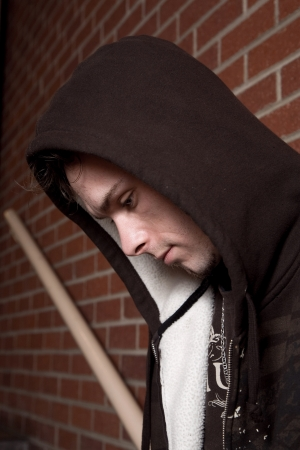 Young troubled looking man wearing a hoodie and in a stairwell.