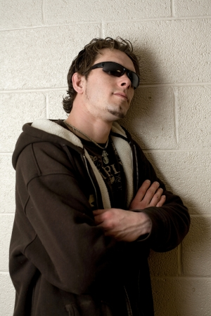 Young man leaning against a cinder block wall. Stock Photo