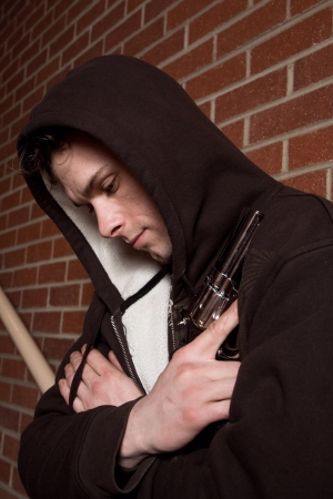 Young dangerous looking man with a firearm wearing a hoodie. Stock Photo - 18444523
