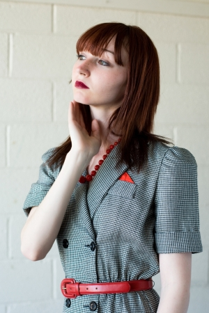 Young red haired woman wearing a retro styled suit