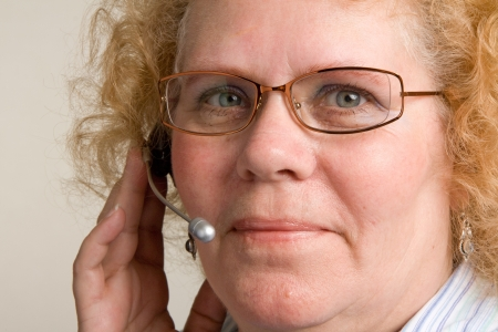 customer service representative: A mature woman taking a call on a hands free telephone headset