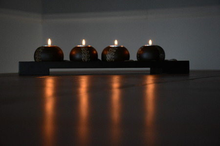 Four candles burn in a dark room