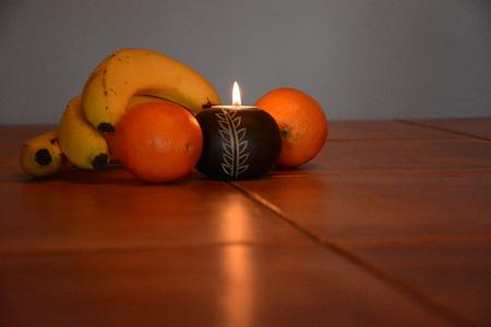 surrounded: Burning candle surrounded by fruit Stock Photo
