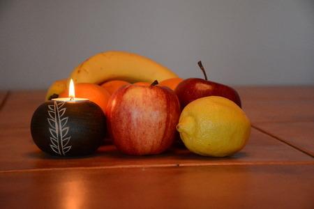 Burning candle illumines fruit