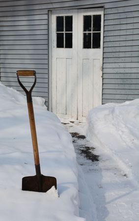 clearing the path: A snow shovel pauses after clearing a path Stock Photo