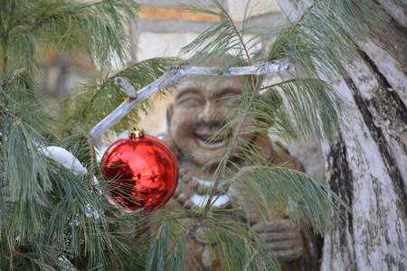 A wooden troll hides behind a Christmas tree decoration