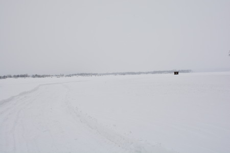 A road on a frozen lake leads to ice-fishing shack