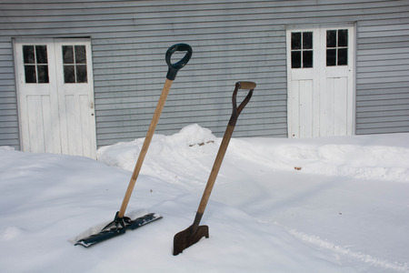 Two snowshovels side-be-side in a snowbank