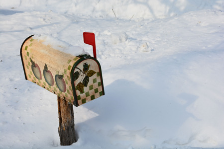 Quaint rural mailbox with red flag up indicates mail inside