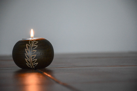 A solo burning candle symbolizes knowledge and hope
