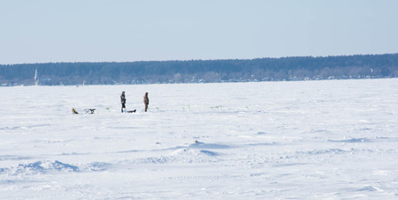 Two hikers enjoy their walk on a frozen northern lake
