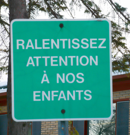 French language traffic warning to protect children: Slow down, watch out for our children.