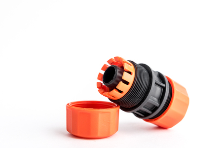 Orange garden water hose nozzle and connectors isolated on white background with soft shadow.
