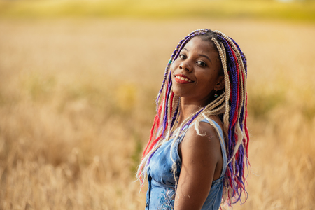portrait of a beautiful young African American girl with a dreddy hairdress on a park background, nature, deciduous forest, photo walk concept in the fresh air