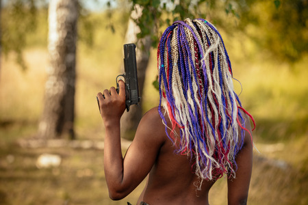 portrait of a beautiful young African American girl with a dreddy hairdress on a park background, nature, deciduous forest, with a gun in her hands. concept of photo walks, female self-defense