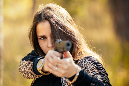 portrait of a beautiful pregnant young girl with a gun in her hands against the backdrop of an autumn forest. Self-defense training. T