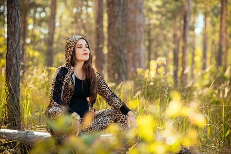 beautiful girl sitting on a tree, picnic in the pine forest. concept photo of natural travelers
