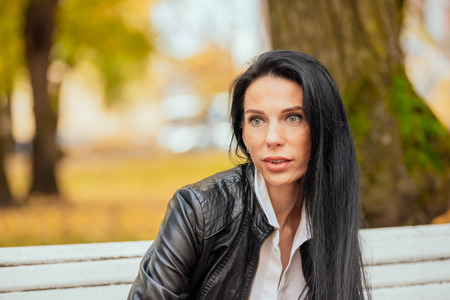 portrait of a beautiful young girl sitting on a bench in an autumn park