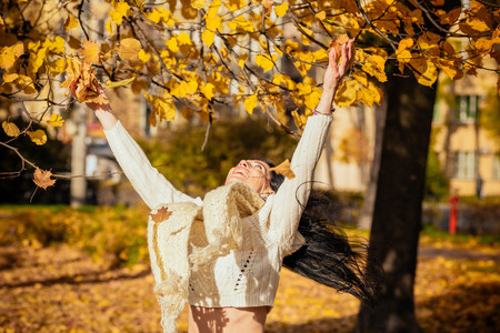 portrait of a beautiful young girl in fashionable business clothes walking along the autumn park, catching the falling leaves
