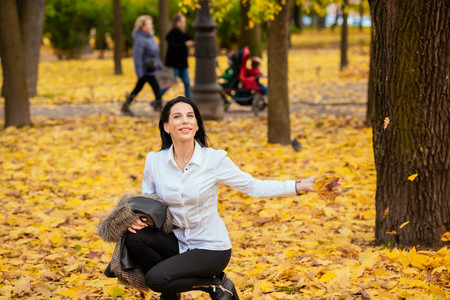 portrait of a beautiful young girl walking along the autumn park in fashionable clothes. Catching the falling yellow and red leaves with hands