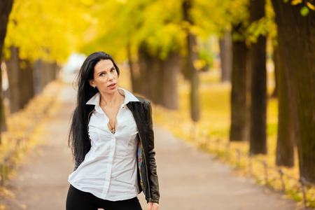 portrait of a beautiful young girl walking in the autumn in a park in fashionable clothes