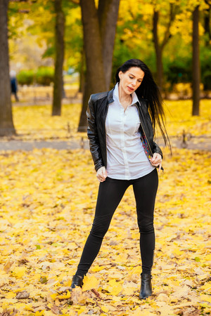 portrait of a beautiful young girl walking along an autumn park in fashionable clothes