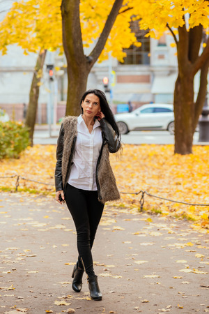 portrait of a beautiful young girl walking along the autumn park in fashionable clothes Archivio Fotografico