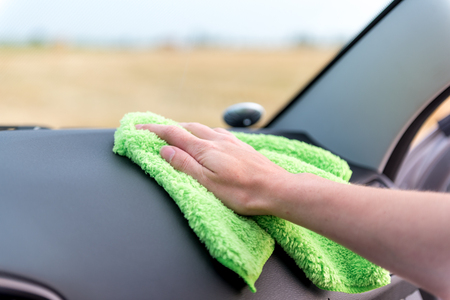 A female hand wipes the panel of a modern auto rag with a microfiber from dust