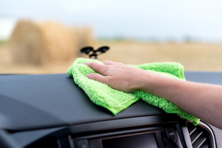 A female hand with a microfibre cloth cleans the panel of a modern car and the radio tape recorder from dust, the concept of professional washing or car wash Stock Photo