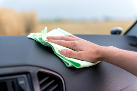 A female hand with a microfibre cloth cleans the panel of a modern car and the radio tape recorder from dust, the concept of professional washing or car wash Archivio Fotografico