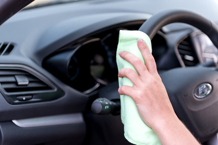A female hand with a microfibre cloth cleans the plastic panel and the wheel of a modern car from dust, the concept of professional washing or car wash
