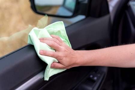 A female hand with a microfiber cloth cleans the plastic door panel of a modern car from dust, a professional washing concept or a car wash