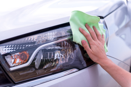 A female hand with a microfibre cloth cleans the headlights, the daytime lights of a modern car from dust, the concept of a professional car wash or car wash Archivio Fotografico