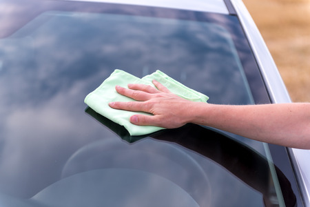 Woman's hand with rag cleaning a silver car's windshield in sunny, cloudy day. Early spring washing or regular wash up. Archivio Fotografico