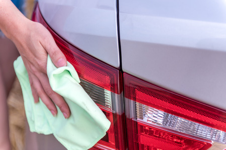 A female hand with a microfibre cloth cleans the tail lights, a stop lamp from dust, a professional wash concept or a car wash