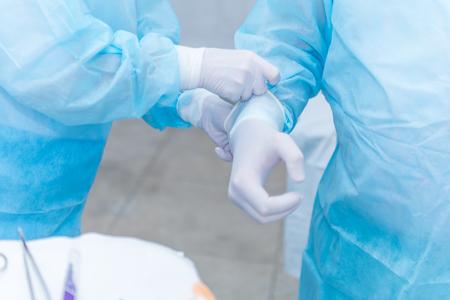 L'assistente del medico aiuta a mettere i guanti sterili in lattice sul chirurgo prima dell'intervento chirurgico in ospedale Archivio Fotografico - 92613278