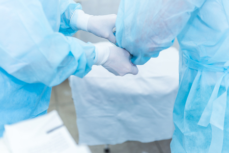 The doctor's assistant helps put the sterile latex gloves on the surgeon before surgery in the hospital