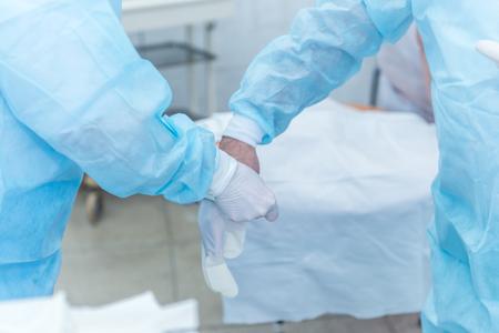 L'assistente del medico aiuta a mettere i guanti sterili in lattice sul chirurgo prima dell'intervento chirurgico in ospedale Archivio Fotografico - 92610218