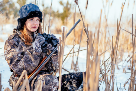 Beautiful girl hunter in camouflage suit with binoculars and a gun sits in the thickets of reeds, looking out for prey