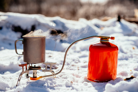 portable gas burner in a winter forest. Bushcraft, hunting and people concept