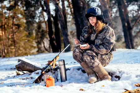 Female hunter preparing food with a portable gas burner in a winter forest. Bushcraft, hunting and people concept