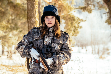 Portrait of a beautiful young girl while hunting in a winter pine forest, with a gun
