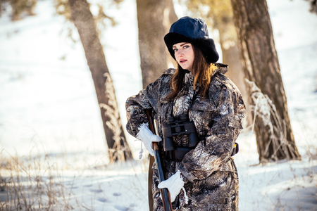 portrait of a beautiful young hunter girl in a winter forest, ready for a shot in the game. Concept photo hunting, camouflage
