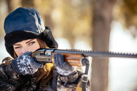 Ritratto di una bella ragazza giovane cacciatore in una foresta d'inverno, pronto per un colpo nel gioco. Concept fotografico da caccia, mimetico Archivio Fotografico - 98280394