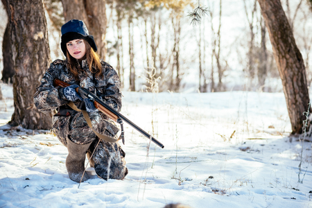 A beautiful hunter in a camouflage suit walks through the woods with weapons, preparing to hunt.