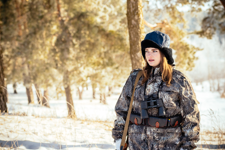 female hunter in camouflage clothes ready to hunt, holding gun and walking in forest. hunting and people concept