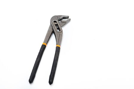 Pliers isolated. Close-up of an closed metal adjustable waterpump pliers with black yellow handles isolated on a white background. Macro photograph.