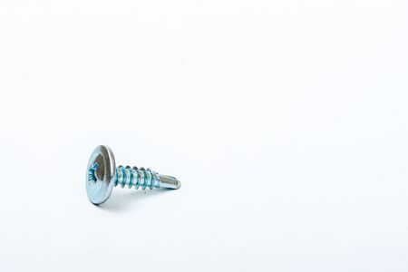 a pile of long woodworking screws on a white background