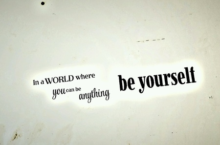 Words printed on a wall about being yourself Stock Photo